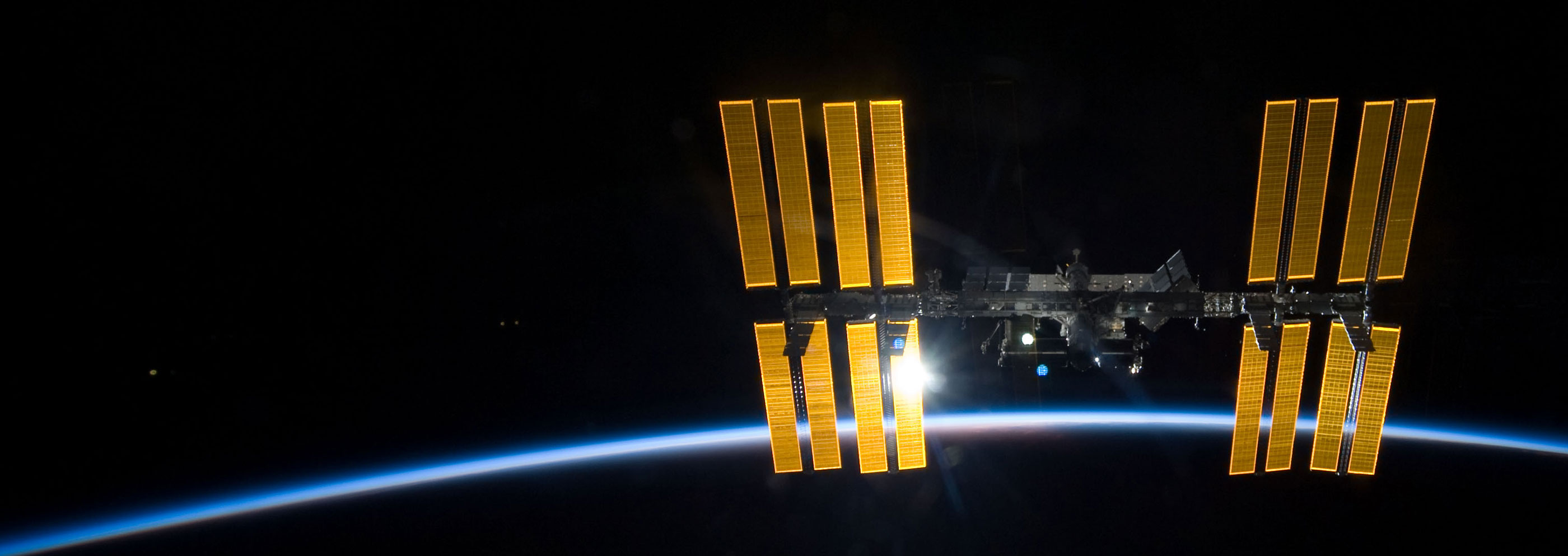 iss illumnated by sun over earth horizon banner