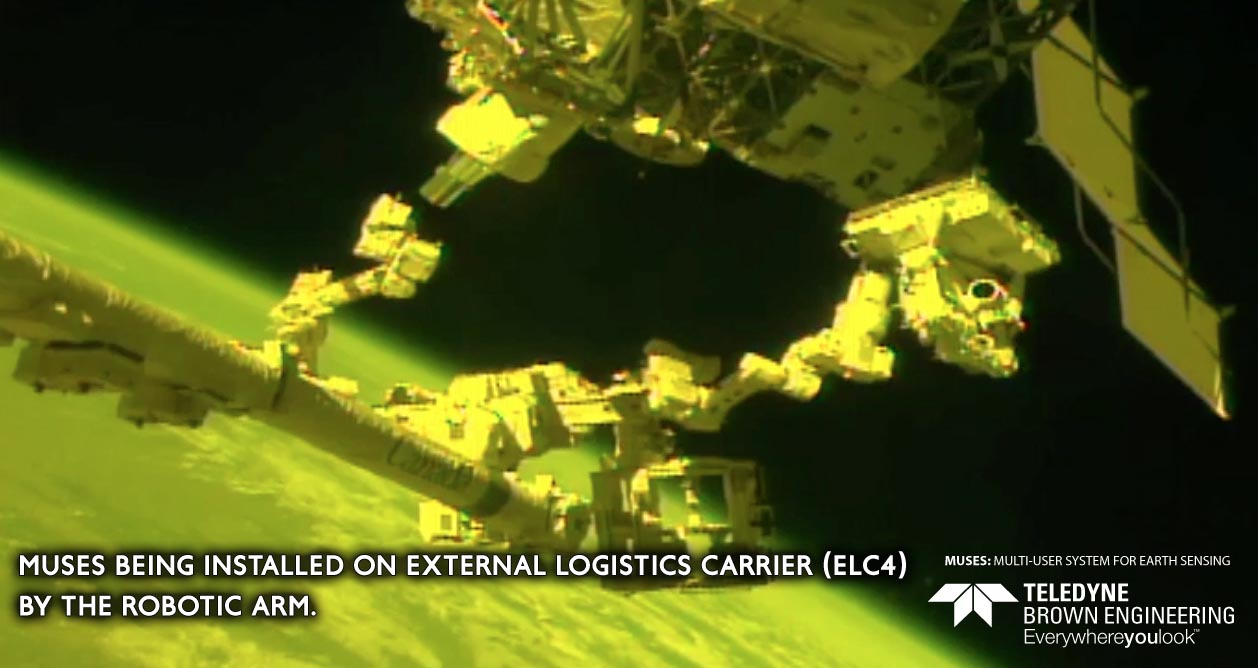 MUSES being installed on the External Logistics Carrier (ELC4) by the robotic arm.
